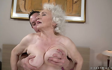 Compressing the boobs of granny Norma while drilling her pussy